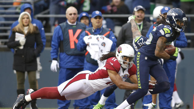 Seattle Seahawks cornerback Richard Sherman (25) runs past Arizona Cardinals wide receiver Larry Fitzgerald (11) as he returns an interception for a 19-yard touchdown during the second quarter of an NFL football game in Seattle, Sunday, Dec. 9, 2012. (AP Photo/John Froschauer)