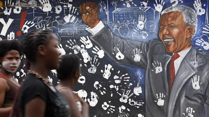 "Young women walk pass a mural depicting former South African President Nelson Mandela at Alexandra township in Johannesburg, South Africa, Tuesday, Dec. 11, 2012. South Africa's presidency says former President Nelson Mandela is suffering from a recurring lung infection and is responding to treatment. The statement Tuesday, Dec. 11, 2012 from presidential spokesman Mac Maharaj said the 94-year-old anti-apartheid icon is ""receiving appropriate treatment and he is responding to the treatment."" (AP Photo/Themba Hadebe)"