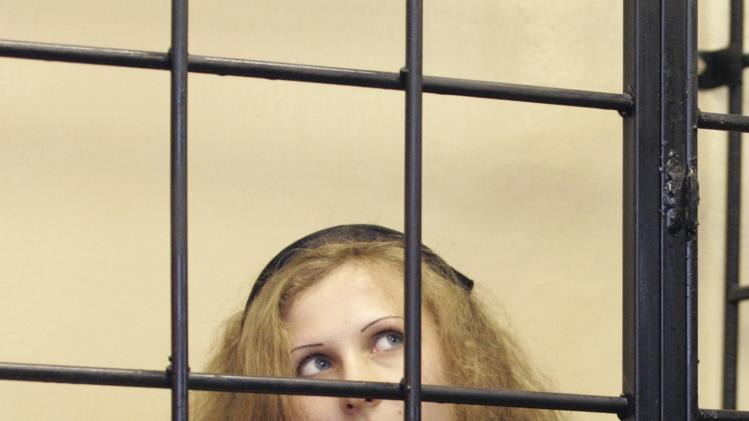 File photo of Alyokhina, jailed member of Russian punk band Pussy Riot, looking out from a defendants' box as she attends a court hearing in Nizhny Novgorod