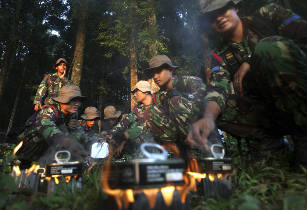 Indonesian soldiers mobilized for search of a missing Russian plane cook food at Taman Nasional Halimun Salak in Sukabumi, West Java, Indonesia, Thursday morning, May 10, 2012. Search and rescue teams