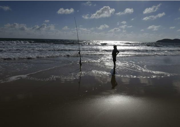 A man fishes in the ocean on the beach in Natal, Brazil