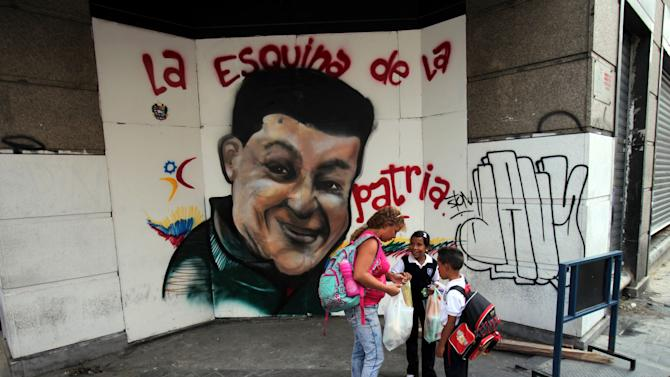 In this Jan. 21, 2013 photo, a woman and children stop for a moment near a mural depicting Venezuela's President Hugo Chavez in Caracas, Venezuela. While Venezuela's sick president recuperates from surgery in Cuba, in Venezuela he is alive and well, at least in spirit. (AP Photo/Fernando Llano)