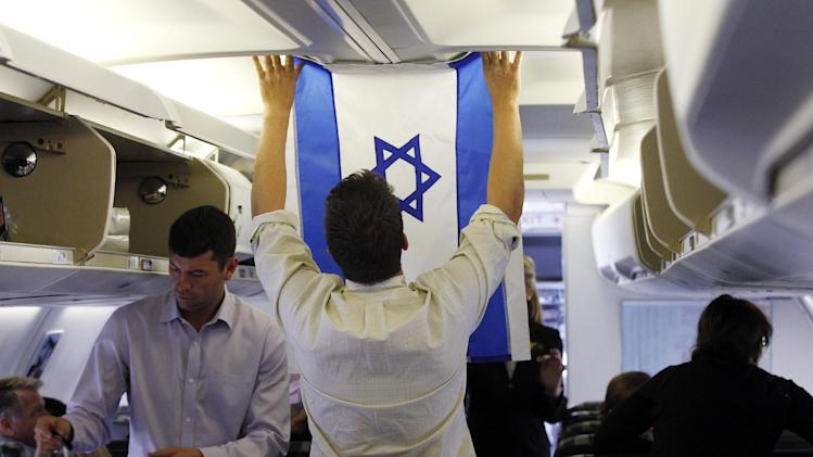 Aide Charlie Pearce examines an Israeli flag on the charter plane of Republican presidential candidate and former Massachusetts Gov. Mitt Romney before he boards at London Stansted Airport, Saturday, July 28, 2012, as he travels to Israel. (AP Photo/Charles Dharapak)