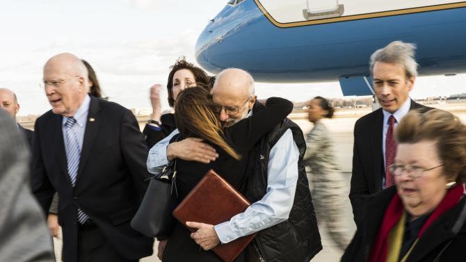 Alan Gross embraces an entourage of family and friends who were awaiting his return from five years of captivity in Cuba to Joint Base Andrews Maryland