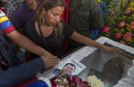Elvira Guzman mourns over the body of her husband, 45-year-old Jose Luis Ponce, a Chavista militant who was allegedly killed on Monday in a confrontation with opposition supporters, as another person places an image of Chavez on his coffin during his wake in Caracas, Venezuela, Wednesday, April 17, 2013. The political heirs of Hugo Chavez filled Venezuela's airways Wednesday with a steady drumbeat of attacks on the man who says they stole the presidency from him. They called opposition leader Henrique Capriles a coup-plotter and said he was inciting post-election violence that had claimed seven lives, including Ponce, and injured 61. Capriles called the government assault a smoke screen to divert attention from his demand for a recount of every ballot from Sunday's election. (AP Photo/Enric Marti)