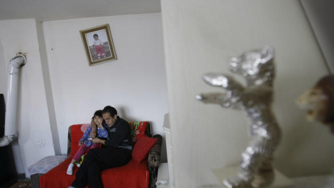 Gypsy actor Nazif Mujic hugs his daughter Sandra in the living room where his Best Actor award - the Silver Bear - decorates the shelf of his shabby home in the village of Poljice, 150 kms northeast of Sarajevo, on Wednesday, April 10, 2013.  People in the Gypsy village  of Poljice say they will never forget the night they almost fell off their chairs two months ago. Did they really hear the elegant woman on TV correctly? Could she really be talking about their neighbor, the toothless man who passed his days selling scrap metal and lived in the shack down the road? The camera switched to a frightened-looking Najif Mujic. Yes it was him. THEIR Nazif _ who had just left Matt Damon and Jude Law in the dust to win the best actor award at the Berlin Film Festival.    (AP Photo/Amel Emric)