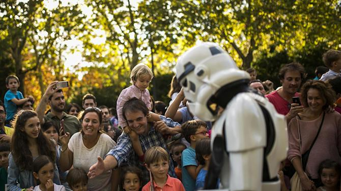 People watch as a reveler dressed as member of the Galactic Empire marches during a Star Wars Parade in Madrid, Spain, Saturday, Sept. 20, 2014. (AP Photo/Andres Kudacki)