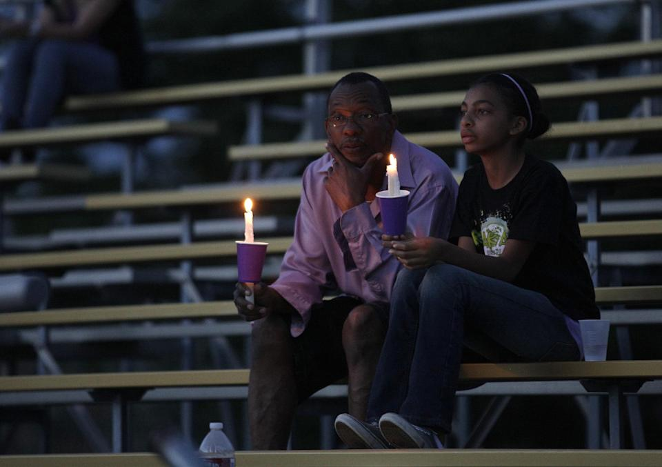 Two people attending a vigil for movie theater shooting victim AJ Boik hold candles Saturday, July 21, 2012, at Gateway High School in Aurora, Colo.(AP Photo/Ted S. Warren)