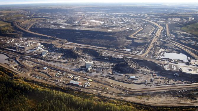 FILE - This Sept. 19, 2011, aerial photo shows a tar sands mine facility near Fort McMurray, in Alberta, Canada. The White House plan to seek alternate routes for a Canada-to-Texas oil pipeline presents a tangle of new problems for the project's backers, and any of those obstacles could still sink the proposal before the first spade of dirt is turned. Shifting the path to avoid a major aquifer could increase the number of perilous stream crossings and put the line closer to populated areas.(AP Photo/The Canadian Press, Jeff McIntosh, File)