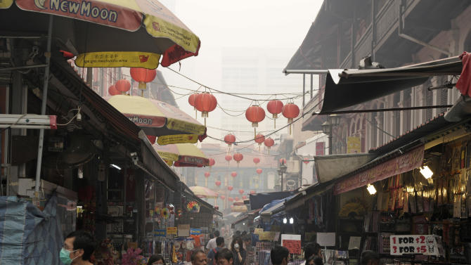 A street in Singapore's Chinatown is covered with a haze on Friday, June 21, 2013. Air pollution in Singapore has soared to record heights for a third consecutive day, as Indonesia prepared planes and helicopters to battle raging fires blamed for hazardous levels of smoky haze in three countries. (AP Photo/Joseph Nair)