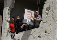 Syrians in a damaged building hold up a portrait of their President Bashar al-Assad as UN observers inspect a nearby Shiite holy shrine in the Sayyida Zeinab suburb of Damascus. Activists call for another day of protests in Syria after at least 52 people were killed in clashes and bombings across the country as the uprising against President Bashar al-Assad enters its 16th month