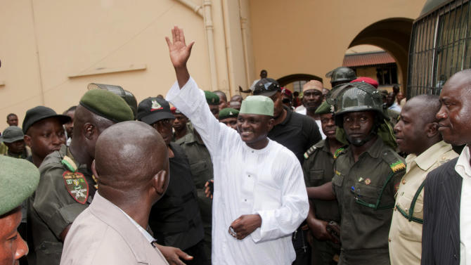 """In this Monday Aug. 8, 2011 photo, Nigeria's former Chief security officer, Maj. Hamza Al-Mustapha, center, waves after his trial at the federal high court in Lagos, Nigeria. Maj. Hamza Al-Mustapha served as the right-hand man of Nigeria's feared and final military dictator, suppressing dissent through fear and once boasting of even having a """"license to kill. Now, after nearly 14 years in prison, he's finally facing trial on charges of orchestrating the murder of a political rival's wife, reopening old wounds from an era of terror in Nigeria.    (AP Photo/Sunday Alamba)"""