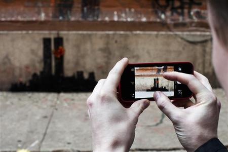 A man takes a picture of an artwork by British graffiti artist Banksy at Lower Manhattan in New York