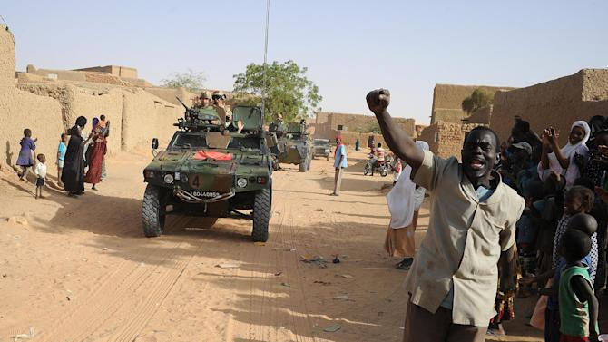 Locals welcome French soldiers on top of a armored vehicles in Bourem, northern Mali, Sunday, Feb. 17, 2013. Mali's military detained eight Arab men last week in Timbuktu, raising fears of further reprisals against the region's Arab minority whose members are accused of having supported the al-Qaida-linked groups which overran northern Mali last year. (AP Photo /Pascal Guyot, Pool)