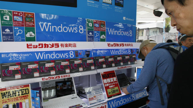 People check Microsoft Windows 8 operation systems at a discount electronic store after the store launched the sales  in Tokyo Friday, Oct. 26, 2012. (AP Photo/Koji Sasahara)