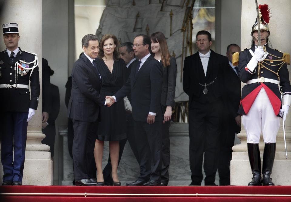 Outgoing French President Nicolas Sarkozy, left, shakes hansd with new President Francois Hollande at the Elysee Palace after the handover ceremony Tuesday, May 15, 2012 in Paris. Behind right are Carla Bruni-Sarkozy and Valerie Trierweiler, center, companion of Francois Hollande. (AP Photo/Michel Euler)