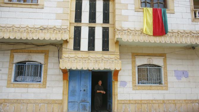 A woman stands on the porch of a house in the northern Syrian town of Kobani