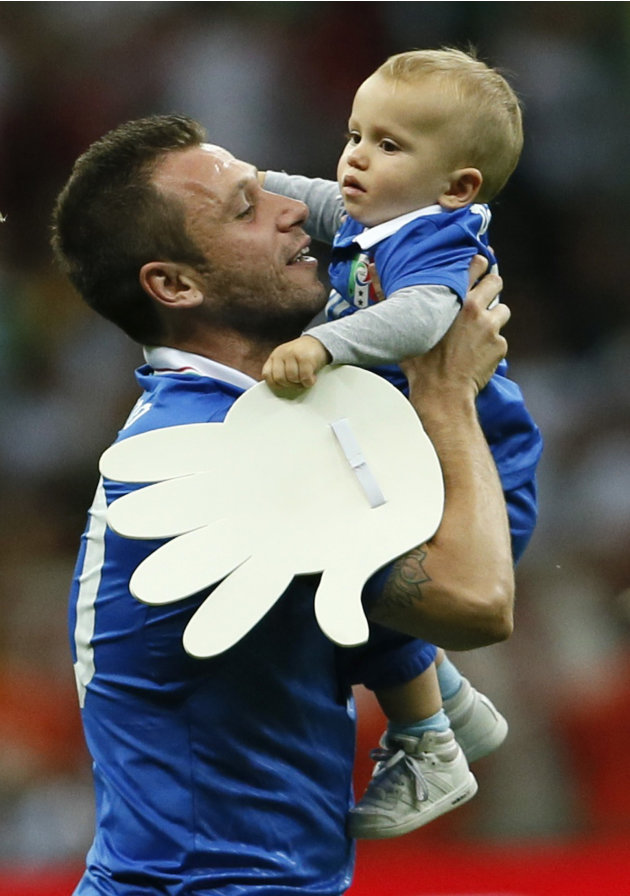 Italy's Antonio Cassano holds his baby at the end of their Euro 2012 semi-final soccer match against Germany in Warsaw