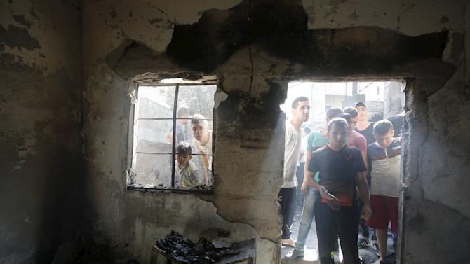 Palestinians inspect the damage to a house following an Israeli army raid in the occupied West Bank city of Jenin