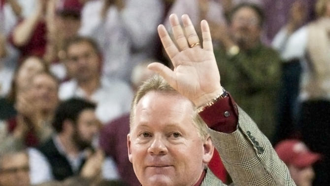 Arkansas football coach Bobby Petrino walks onto center court to be recognized for his team's 11-2 season during halftime of an NCAA college basketball game between Arkansas and Michigan in Fayetteville, Ark., Saturday, Jan. 21, 2012. (AP Photo/April L. Brown)