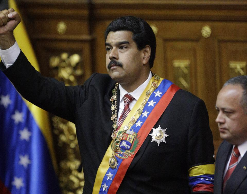 Nicolas Maduro raises his fist after he was sworn in as Venezuela's acting president by the President of the National Assembly, Diosdado Cabello, right, at the National Assembly in Caracas, Venezuela, Friday, March 8, 2013. (AP Photo/Fernando Llano)