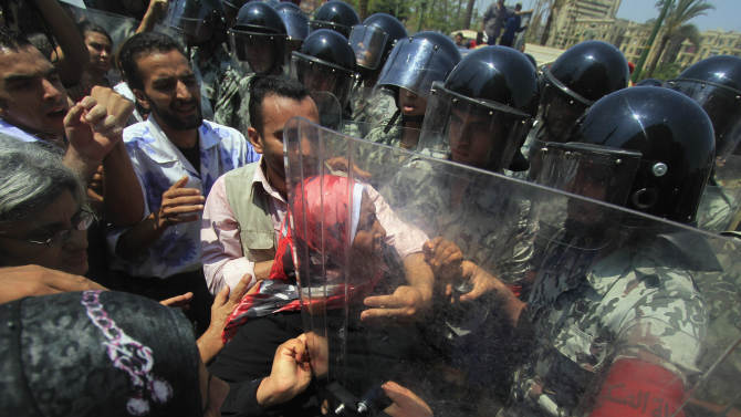 Demonstrators confront military police as they try to reach Tahrir Square to hold a protest in memory of protester Mohammed Mohsen, who died on Wednesday from wounds received during clashes in the Abbasiyah area of Cairo on July 23, in downtown Cairo, Egypt Friday, Aug. 5, 2011. (AP Photo/Khalil Hamra)
