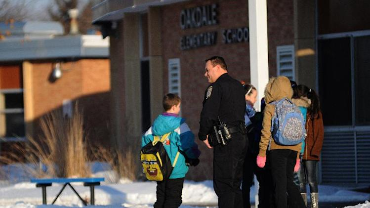 Oakdale police officer Brian Stroshane stands with students at Oakdale Elementary School in Oakdale, Minn., where 9-year-old shooting victim Devin Aryal was a student, on Tuesday, Feb. 12, 2013.  Stroshane was at the school to reassure the students that school is a safe place. (AP Photo/The Star Tribune, Richard Sennott)  MANDATORY CREDIT; ST. PAUL PIONEER PRESS OUT; MAGS OUT; TWIN CITIES TV OUT