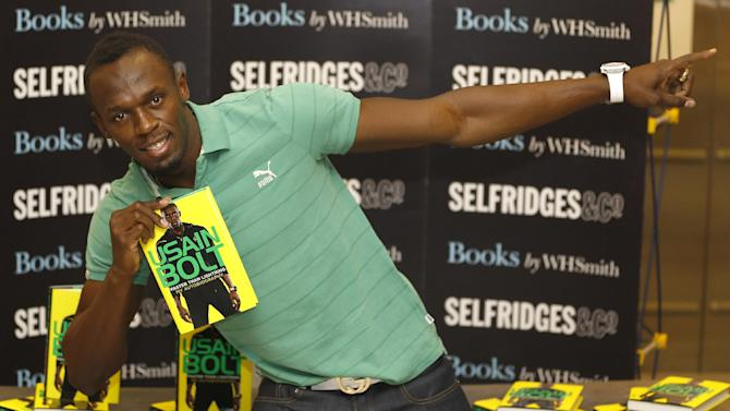Jamaican athlete Usain Bolt poses for the media with a copy of his new autobiography called 'Faster than Lightning' at a department store in London, Thursday, Sept. 19, 2013. (AP Photo/Kirsty Wigglesworth)