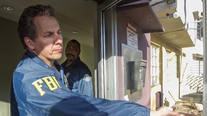 Law enforcement agents, FBI agent Scott Garriola, left, and LAPD Sgt. Anthony Verret, right, enter the apartment building where LAPD and an FBI task force arrested 26-year-old Ammar Harris, who is accused in the Feb. 21 deaths of three people on the Las Vegas strip, in the Studio City area of Los Angeles Thursday, Feb. 28, 2013. The 26-year-old is a self-described pimp who was the subject of a multi-state manhunt following the Feb. 21 gunfire and chain-reaction crash that killed three and injured at least five. (AP Photo/Damian Dovarganes)