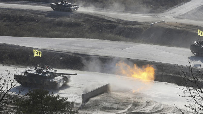 A South Korean K1 army tank fires live rounds during an exercise at Seungjin Fire Training Field in mountainous Pocheon, South Korea, near the border with North Korea, Wednesday, March 27, 2013. North Korea said Wednesday that it had cut off a key military hotline with South Korea that allows cross border travel to a jointly run industrial complex in the North, a move that ratchets up already high tension and possibly jeopardizes the last major symbol of inter-Korean cooperation.(AP Photo/Yonhap, Lim Byung-shick)  KOREA OUT