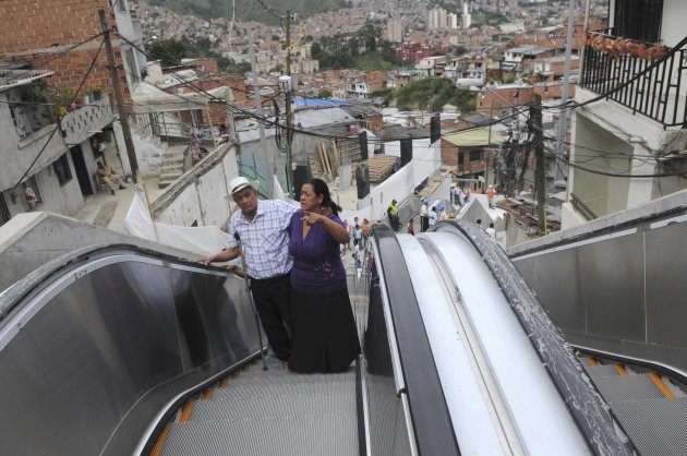 Luis Hernesto Holguin, left, and his sister Resfa Holguin use outdoor escalators, newly installed at Comuna 13 shantytown as part of an urbanization plan to improve living conditions of residents, in Medellin, Colombia, Dec. 26, 2011. (AP Photo/Luis Benavides)