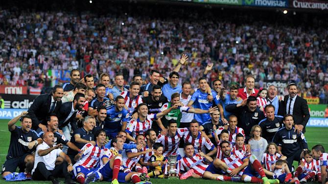 Atletico Madrid's players and staff pose on the pitch with the Super Cup trophy at the end of their Spanish Supercopa second-leg match against Real Madrid, at the Vicente Calderon Stadium in Madrid, on August 22, 2014