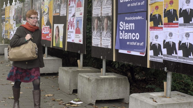 In this photo taken on Monday, Oct. 8, 2012, a woman walks by election campaign posters in Antwerp, Belgium. Historic world port and hip fashionista capital, Antwerp has always lived on the crest of the wave. Now, a separatist Fleming is seeking to make the city his own on Sunday and use it as a base for breaking away from Belgium. Local elections will take place on Sunday, Oct. 14, 2012. Poster reads on second right, 'Vote Blank and annul the election'. (AP Photo/Virginia Mayo)