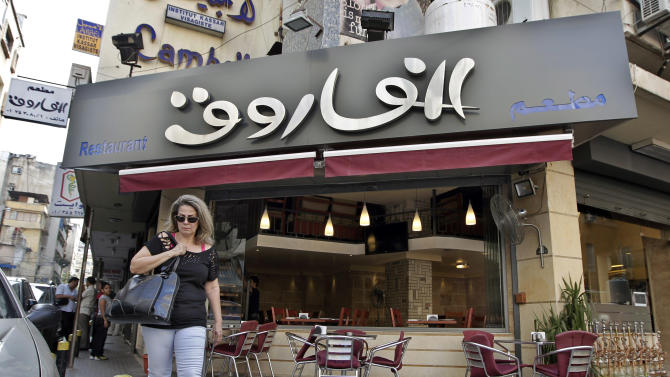 In this Monday, Sept. 30, 2013 photo, a Lebanese woman walks past the Syrian Al-Farouk restaurant in Hamra Street, Beirut, Lebanon. On Hamra street, some stores and restaurants including Damascus' famous Al-Farouk food establishment that relocated to Beirut earlier this year almost exclusively employ Syrians, including chefs, waiters, managers, and cleaners. Lebanon's market is flooded with Syrian refugees in desperate need of work, their cheap labor force posing an additional problem to the Lebanese economy that has struggled with billions of losses from spillover effects of the Syrian conflict. (AP Photo/Bilal Hussein)