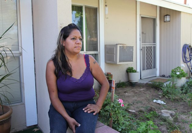 This photo taken Saturday June 1, 2013, in Fresno, Calif. shows farmworker Cristina Melendez posing for a photo in front of her mother's apartment. A Mexico native who came to the U.S. at age 13, Melendez and her seven U.S. citizen children have for years struggled with poverty in the San Joaquin Valley, one of the richest agricultural regions in the world. (AP Photo/Gosia Wozniacka)
