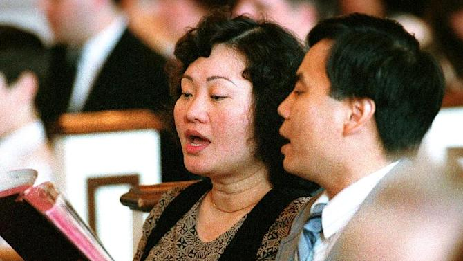FILE - In this May 25, 1992 file photo, Phan Thi Kim Phuc and her husband, Bui Huy Toan, sing during a service at the Faithway Baptist Church in Ajax, Ontario, Canada. The couple met in Cuba where Kim Phuc was sent from Vietnam to study in 1986. Phuc, who was the main subject in Associated Press photographer Nick Ut's iconic image of the aftermath of a June 8, 1972 napalm attack in Vietnam, was granted political asylum in Canada in 1992. (AP Photo/Nick Ut)