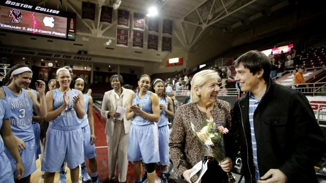 North Carolina coach Sylvia Hatchell gets flowers from her son Van as her team looks on after North Carolina defeated Boston College 80-52 in an NCAA college basketball game in Boston on Thursday, Feb. 7, 2013. Hatchell earned her 900th career victory. (AP Photo/Winslow Townson)