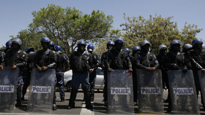 Police officers look on as firebrand politician Julius Malema, unseen, addresses supporters after appearing at the Magistrate's Court in Polokwane, South Africa, Wednesday, Sept.  26, 2012, on charges of money laundering in connection with an improper government tender awarded to a company his family trust partly owns. (AP Photo/Themba Hadebe)