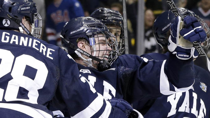 Yale's Clinton Bourbonais, center, celebrates after his goal during the first period of the NCAA men's college hockey Frozen Four national championship game against Quinnipiac in Pittsburgh, Saturday, April 13, 2013. (AP Photo/Gene Puskar)