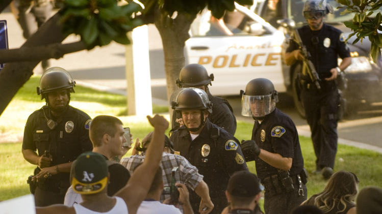 A group of Anaheim police officers try to hold back a crowd of protesters as they wait reinforcements Tuesday afternoon July 25, 2012, in Anaheim, Calif.  Back-to-back weekend shootings by police have sparked four days of protests. (AP Photo/The Orange County Register,Paul Rodriguez )   MAGS OUT; LOS ANGELES TIMES OUT
