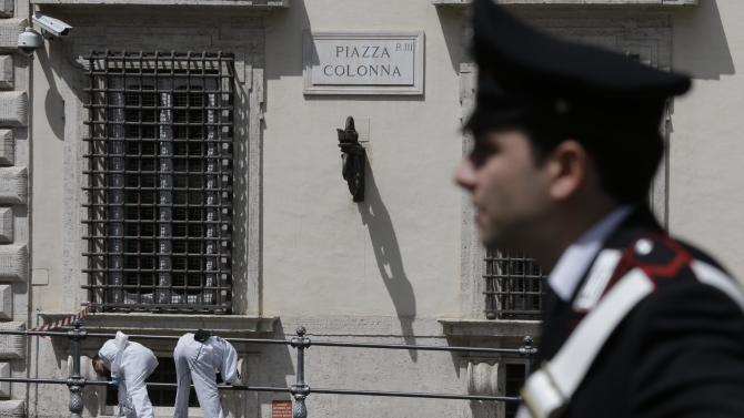Forensic police study the area where a shooting took place outside Chigi Palace, premier's office, in Rome, Sunday, April 28, 2013. Two Italian paramilitary policemen were shot and wounded Sunday in a crowded square outside the premier's office in Rome as Italy's new leader Enrico Letta was being sworn in at the Quirinal presidential office, about a kilometer (half-mile) away. It was not immediately clear if there was any connection between the shooting and the swearing-in. (AP Photo/Alessandra Tarantino)