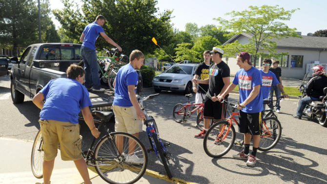 "This May 22, 2012, photo shows students loading bikes into a truck during an organized bike ride to Kenowa Hills High School in Walker, Mich. The 65 graduating students who participated thought they were having harmless fun but in the principal's mind they had broken the ""no pranks"" rule and suspended them. The strict edict eventually caused parents, students and even the town's mayor to ask: Where should schools draw the line? The principal later apologized. (AP Photo/The Grand Rapids Press, Chris Clark)"