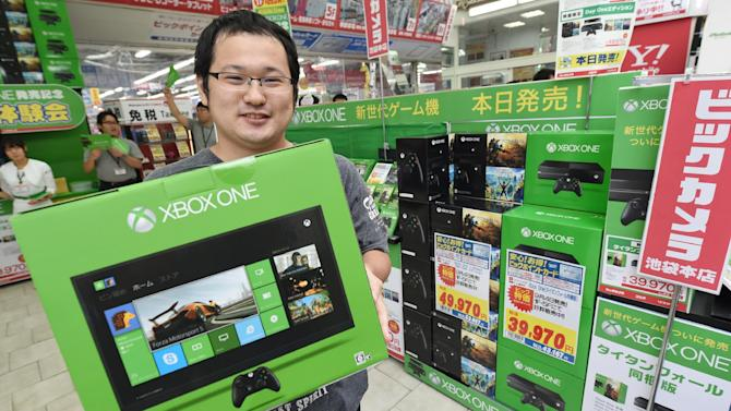 A customer holds a box containing Microsoft video game console Xbox One, at a household appliance shop in Tokyo, on September 4, 2014