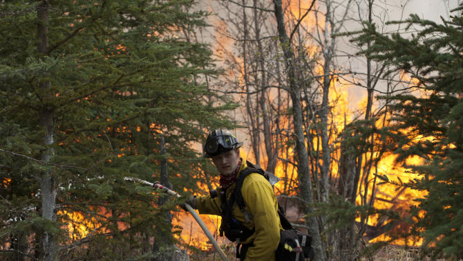 Central Emergency Services firefighter Spencer Mclean works to contain a portion of a wildfire near the Funny River neighborhood Sunday, May 25, 2014, in Soldotna, Alaska. A massive wildfire pushed by wind in Alaska's Kenai Peninsula south of Anchorage continued to explode in size, leading to mandatory evacuations of 1,000 structures, officials said Sunday. (AP Photo/Peninsula Clarion, Rashah McChesney)