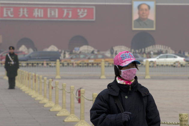 A woman wears a mask as she visits Tiananmen Square in Beijing Sunday, Jan. 13, 2013. People refused to venture outdoors and buildings disappeared into Beijing's murky skyline on Sunday as the capital