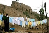 "A woman hangs clothes to dry in her backyard, which forms part of the Puruchuco archaeological site in Lima. Huacas ""for the most part are not protected, which is why they have been invaded by families without homes, or turned into dumps or refuges for delinquents,"" archeologists says"