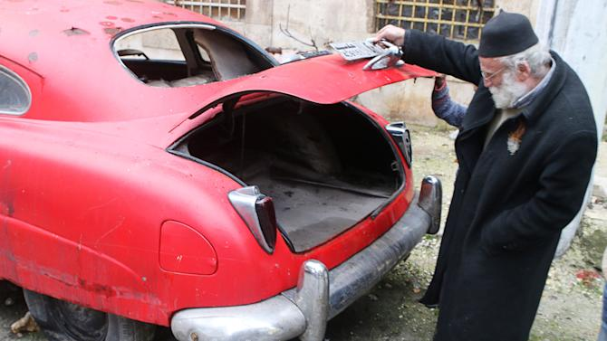 Mohamed Badr al-Din opens the trunk of one of his vintage cars along a street where they are kept, in the al-Shaar neighborhood of Aleppo
