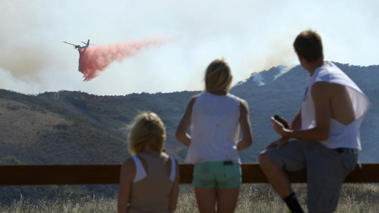 Residents watch an air tanker drop fire retardant during a wildfire that burned several thousand acres, Thursday, May 2, 2013, in Ventura County, Calif.   (AP Photo/Mark J. Terrill)