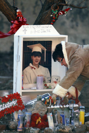 Christine Piacentini straightens up a makeshift memorial for her daughter, homicide victim Nicole Piacentini, in the Kensington neighborhood of Philadelphia, Tuesday, Dec. 21, 2010.  Police in Philadelphia are pleading with residents not to become vigilantes as the search continues for a man accused in two stranglings and several other attacks. (AP Photo/Matt Rourke)