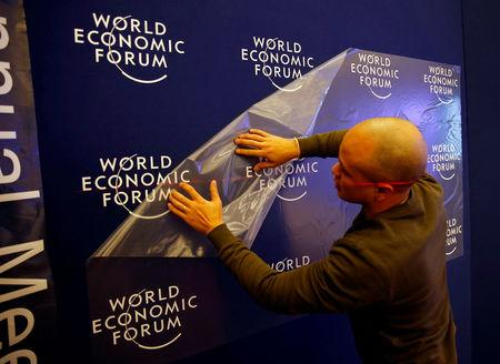 A worker prepares the logo of the World Economic Forum in the congress center of the annual meeting of the World Economic Forum (WEF) in Davos